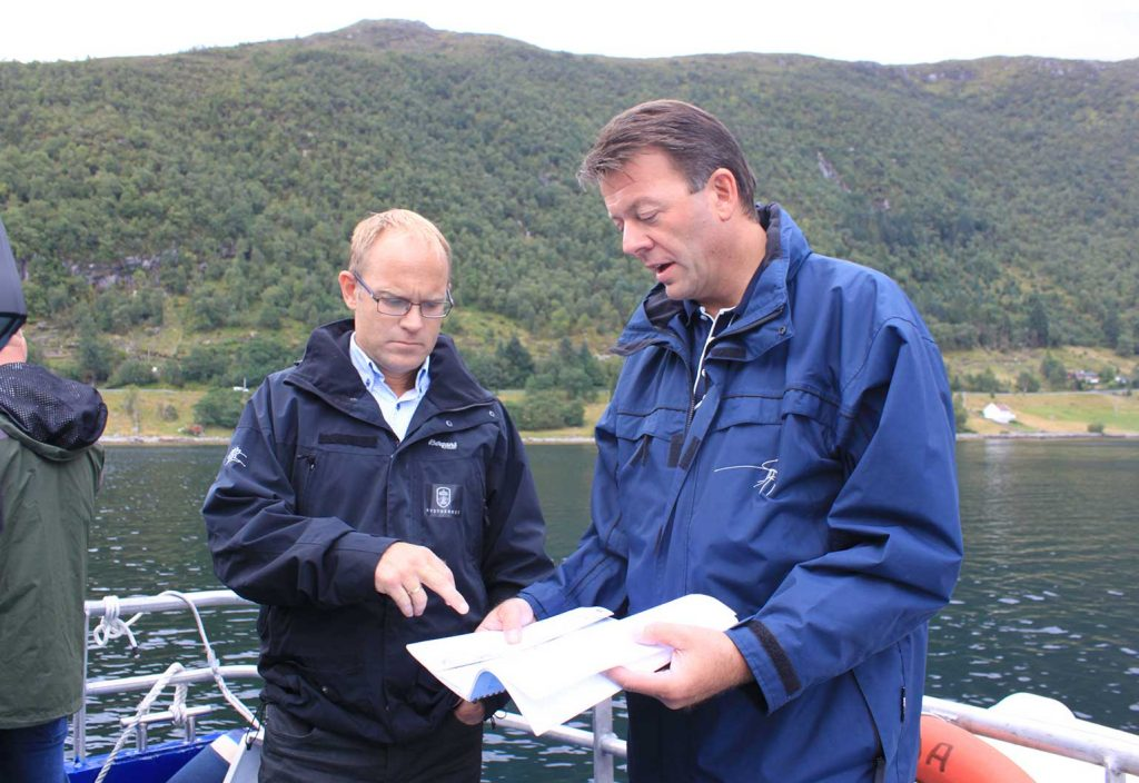 The Norwegian Coastal Administration's Jarle Strand (project owner) and Terje Andreassen (project manager) studying the drawings in front of the site where the southern tunnel section is planned. (Image: Pål Are Lilleheim/ Norwegian Coastal Administration)
